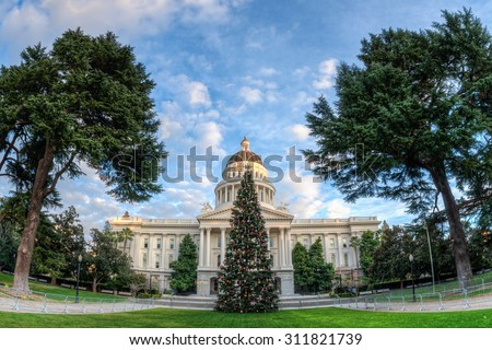 Christmas tree in front of the California State Capitol building in Sacramento. Fisheye lens was used creating a extreme wide angle view of the Capitol. - stock photo