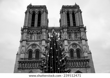 Christmas tree in front of the Notre Dame cathedral in cloudy day. Paris, France. Aged photo. Black and white. - stock photo