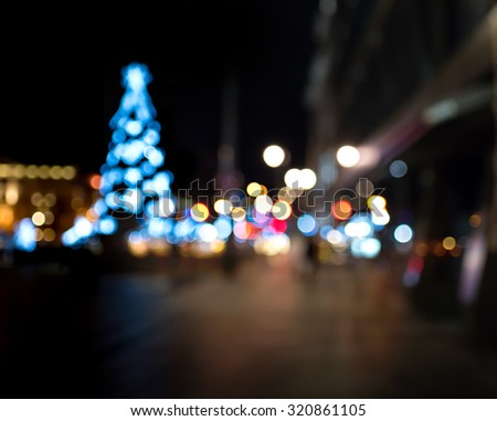 Christmas tree in the city square. Abstract dark blurry urban background.  - stock photo