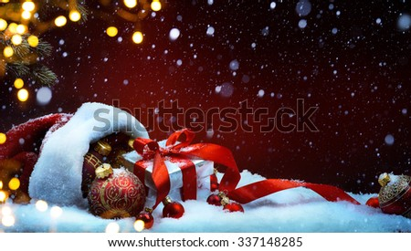 Christmas tree light; festive background with Christmas balls and gift box on snow - stock photo