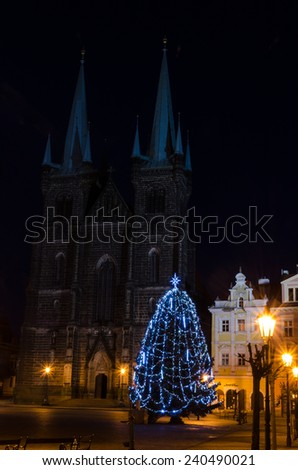 Christmas tree lit in the square, the church in the background - stock photo