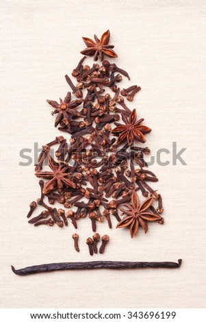 Christmas tree made from brown spices vanilla pods anise stars and cloves on burlap background - stock photo