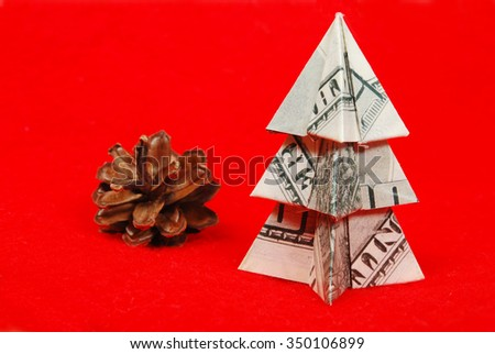 Christmas tree made of hundred dollar bills on a red background - stock photo