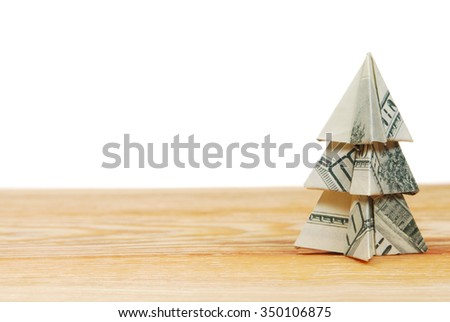 Christmas tree made of hundred dollar bills on a wooden board on a white background - stock photo