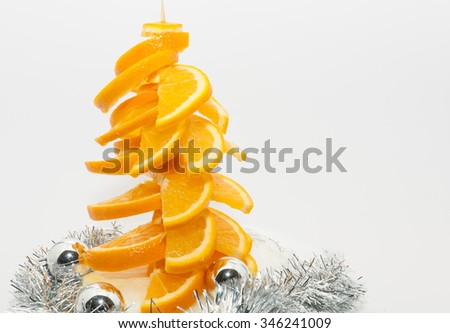 Christmas tree made of Orange fruit with silver ornaments at bottom on white background - stock photo