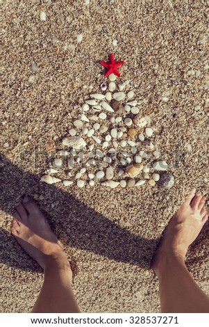 Christmas tree made of pebbles and seashells with a red starfish on top of it and human feet standing next to it - stock photo