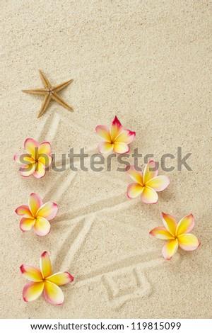 Christmas tree made of sand and frangipani flowers. Xmas beach holiday concept - stock photo