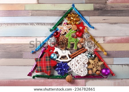 christmas tree made of various colorful decorations on old wooden background - stock photo