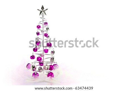 Christmas tree made out of pink and silver jingle bells on pink shimmery fabric - stock photo