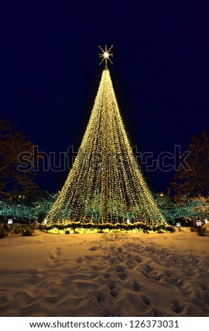 Christmas tree made up of glowing warm lights with snow - stock photo