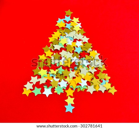 Christmas tree made up of paper stars isolated on red background, selective focus.  - stock photo