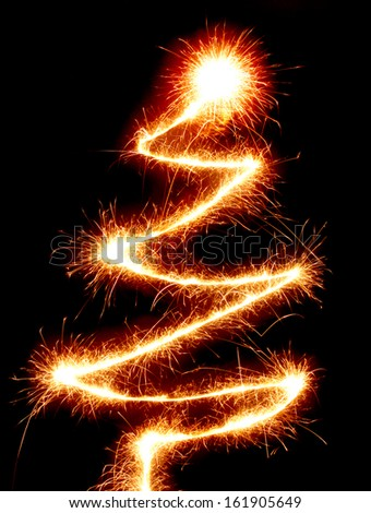 Christmas tree made with a sparkler isolated on black background conceptual symbol - stock photo