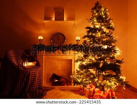 Christmas tree near fireplace in room - stock photo