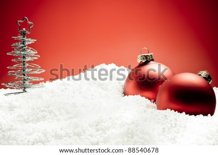 christmas tree near red decoration balls on snow