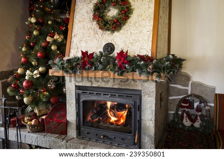 Christmas tree next to burning fireplace in a restaurant - stock photo