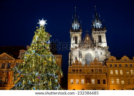 Christmas tree on Old Town Square in Prague with church tower in the background - stock photo