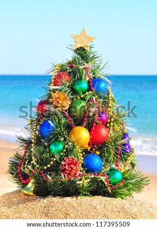 Christmas tree on the sand in the beach - stock photo