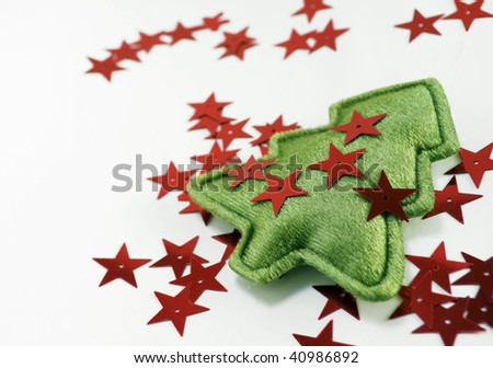 Christmas tree ornament with red sequin stars scattered around, isolated on white, shallow DOF with focus on foreground and copy space at left - stock photo
