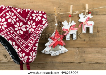 Christmas tree ornaments and red wool winter hat hanging on clothesline. Wooden wall as background.