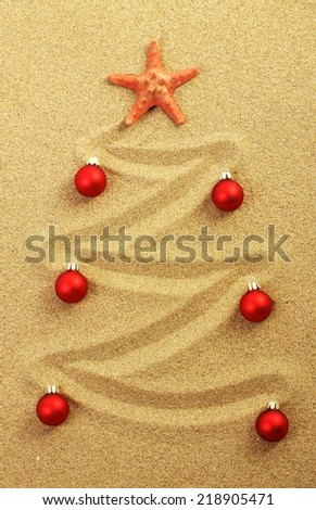 Christmas tree painted in sand with red starfish and red matt christmas balls  - stock photo