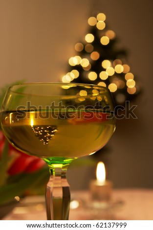 Christmas tree reflected upside down in a wine glass - stock photo