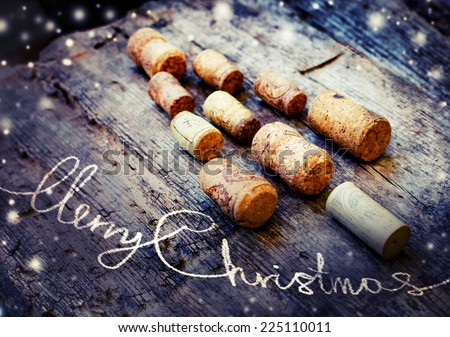 Christmas tree shaped by corks on wooden background - stock photo