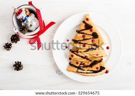 Christmas tree shaped sweet pancakes for a fun holiday breakfast on white table, top view