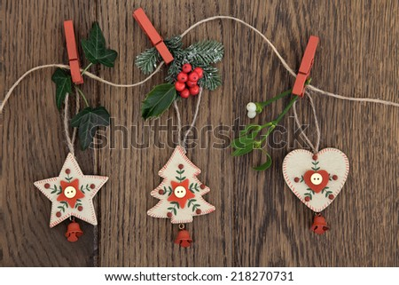 Christmas tree, star and heart decorations with holly, ivy, fir and mistletoe hanging on a string line over oak background. - stock photo