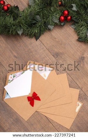 Christmas tree toys and  decoration like envelopes with red bows  with white clear sheet s of paper  and fir branch on wooden table top view  with copy place - stock photo