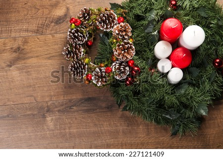 Christmas tree toys  and decoration like  wreath of cones apples and fir branches with red and white candles  on wooden table with  top view  with copy place  - stock photo