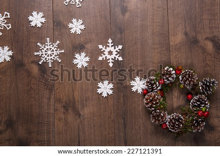 Christmas tree toys  and decoration like  wreath of fir branches and apples and cones   and on wooden table with white  snowflakes with   top view  and  copy place - stock photo