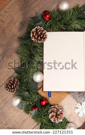 Christmas tree toys  and decoration like  wreath of fir branches and cones and clear sheet  of paper  with pen on wooden table with  top view  and  copy place - stock photo