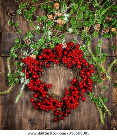 Christmas tree twigs and red berries wreath on wooden texture. Advent decoration. Vintage style toned picture