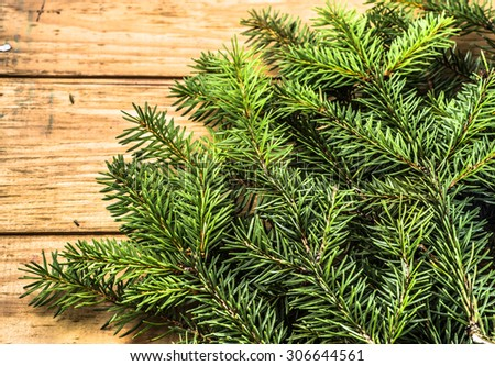 Christmas tree twigs of spruce arranged on rustic wooden planks background useful as holiday background in vintage style. - stock photo