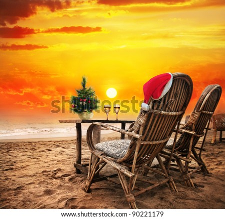 Christmas tree, Two glasses of champagne and Christmas hat on the chair on the beach with view to the ocean  and orange sunset sky in Goa, India - stock photo