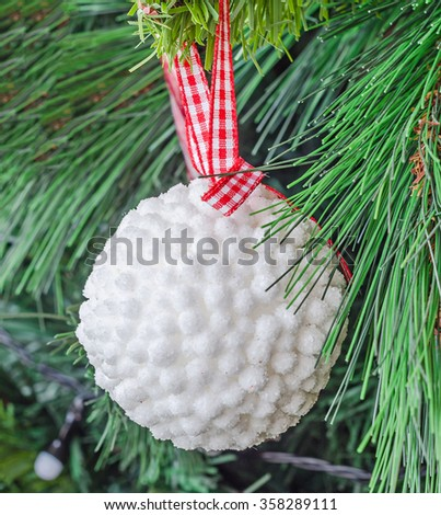 Christmas tree white ornament, globe hanging, snow flake, green tree, firs, close up. - stock photo