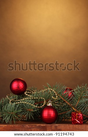 Christmas tree with beautiful New Year's balls on wooden table on brown background