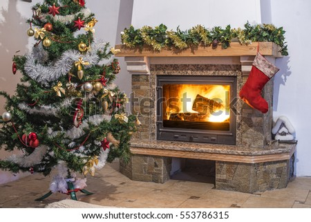 Christmas tree with Christmas decorations and a Glowing fireplace