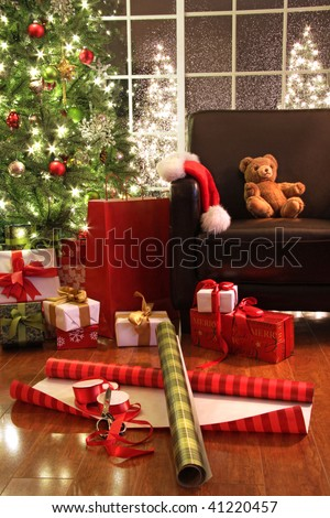 Christmas tree with gifts and teddy bear on chair - stock photo