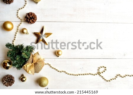 Christmas tree with gold ornaments on white wooden background