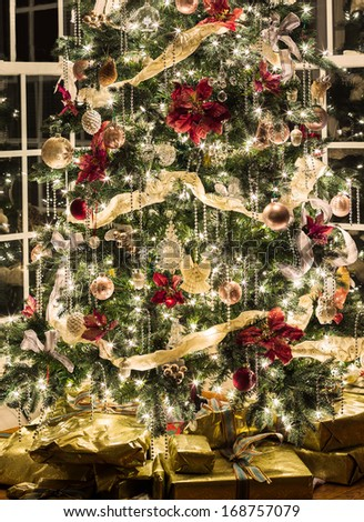 Christmas tree with gold wrapped gifts and presents and lights reflecting in windows around the tree in modern home - stock photo