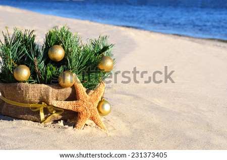 Christmas tree with golden christmas balls and starfish on the sand on the beach - stock photo