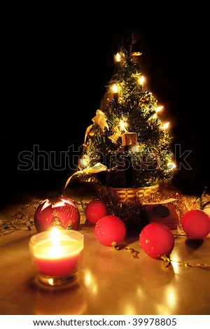 Christmas tree with lights and candles over black