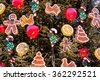 Christmas tree with ornaments of baubles, snowflakes, teddy bears, sleighs, gingerbread man, pine cones and lights. - stock photo
