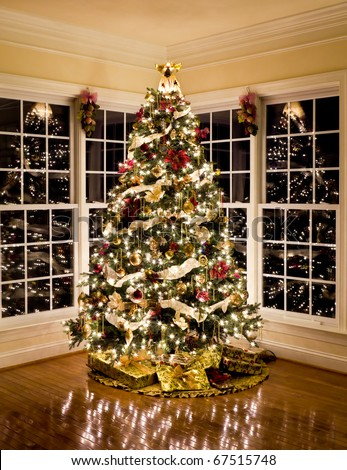 Christmas tree with presents and lights reflecting in windows around the tree in modern home