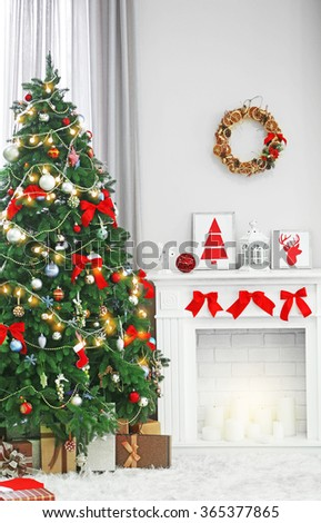 Christmas tree with presents near the fireplace in a room - stock photo
