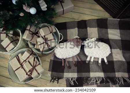 Christmas tree with presents underneath and toys sheep - stock photo