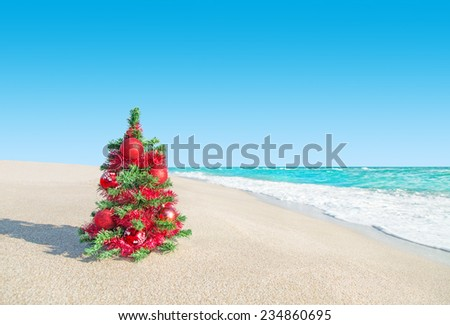 Christmas tree with red decorations at sea beach. New Years vacation concept. - stock photo