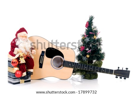 Christmas tree with Santa Claus sitting on present in front of guitar, isolated on white background - stock photo