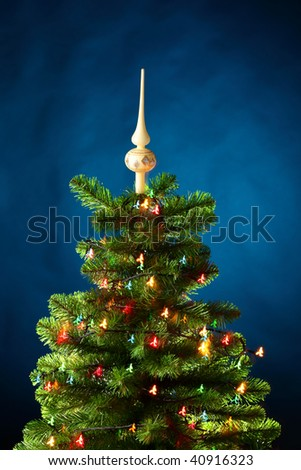 Christmas-tree with shining lamps, blue background - stock photo
